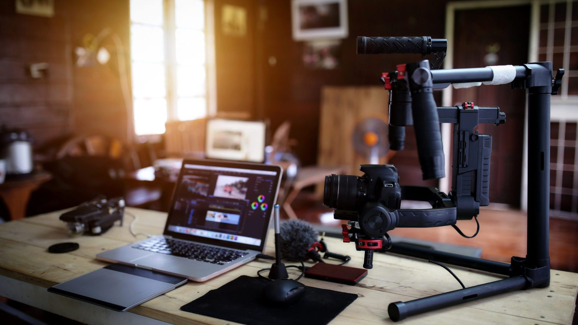 Gaming channel YouTuber equipment laid out on desk including camera, macbook, microphone, and drawing tablet