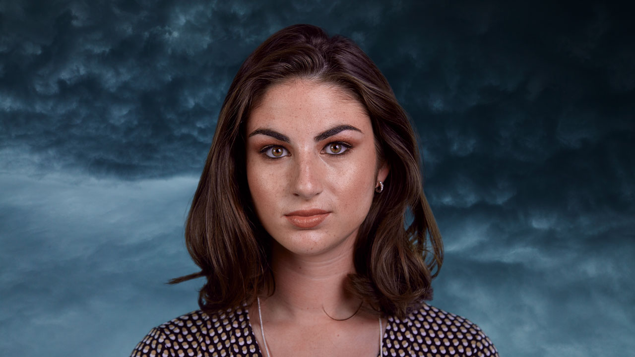 Green screen composite of woman in front of clouds background