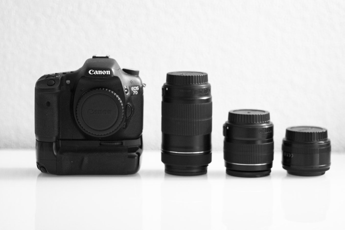 Canon EOS 7D DSLR camera with battery pack and three interchangeable lenses