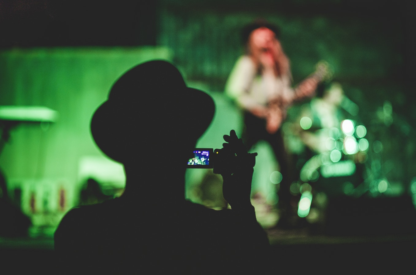 Man in hat recording video at gig - Choosing the best video camera for beginners