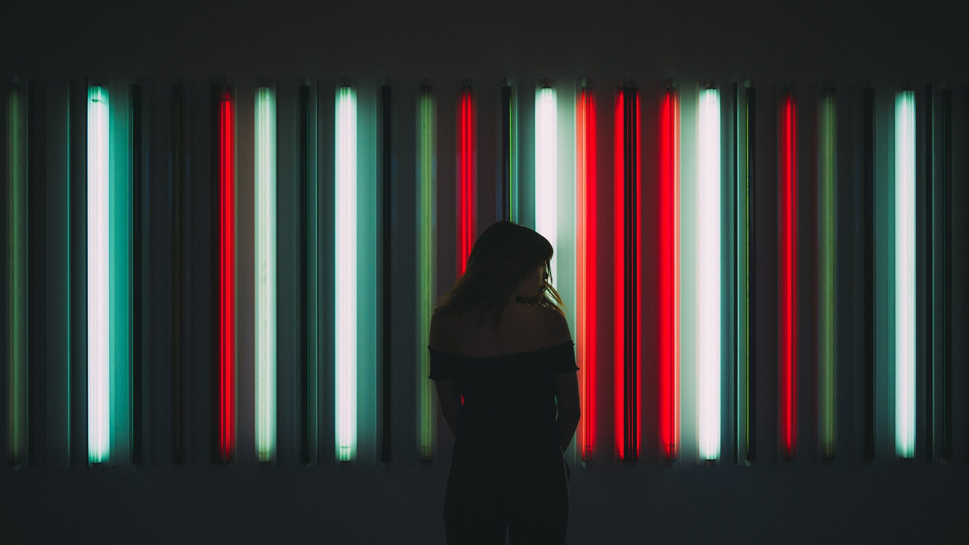 Abstract street photography of girl silhouette in front of red, white, and green striped lighting installation