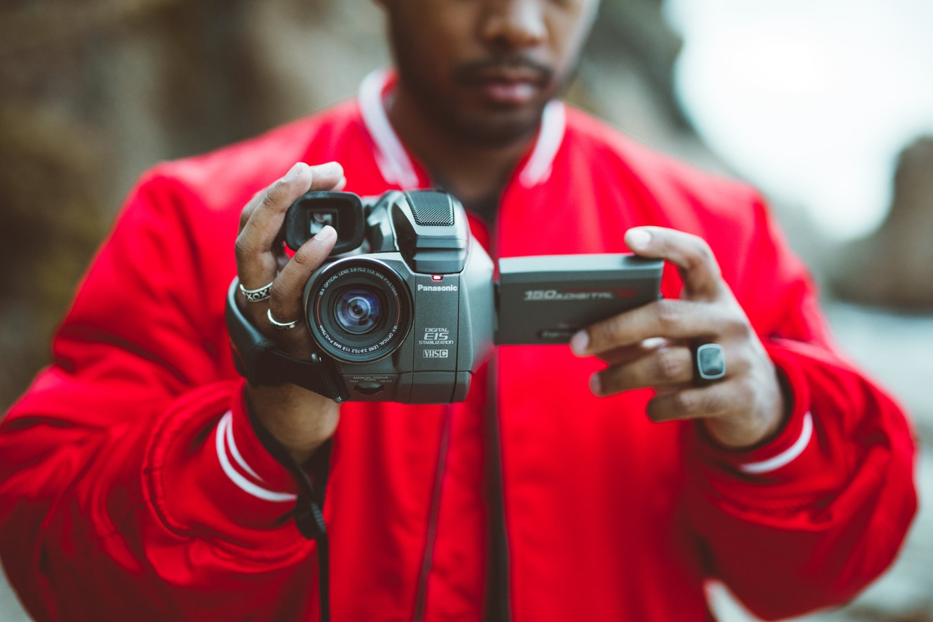 Guy holding camcorder toward camera - choosing the best video camera for beginners