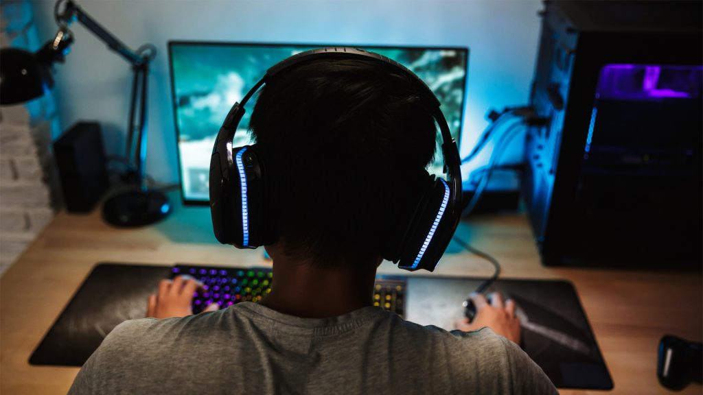 Gamer playing video games on PC with LED headphones and LED gaming keyboard