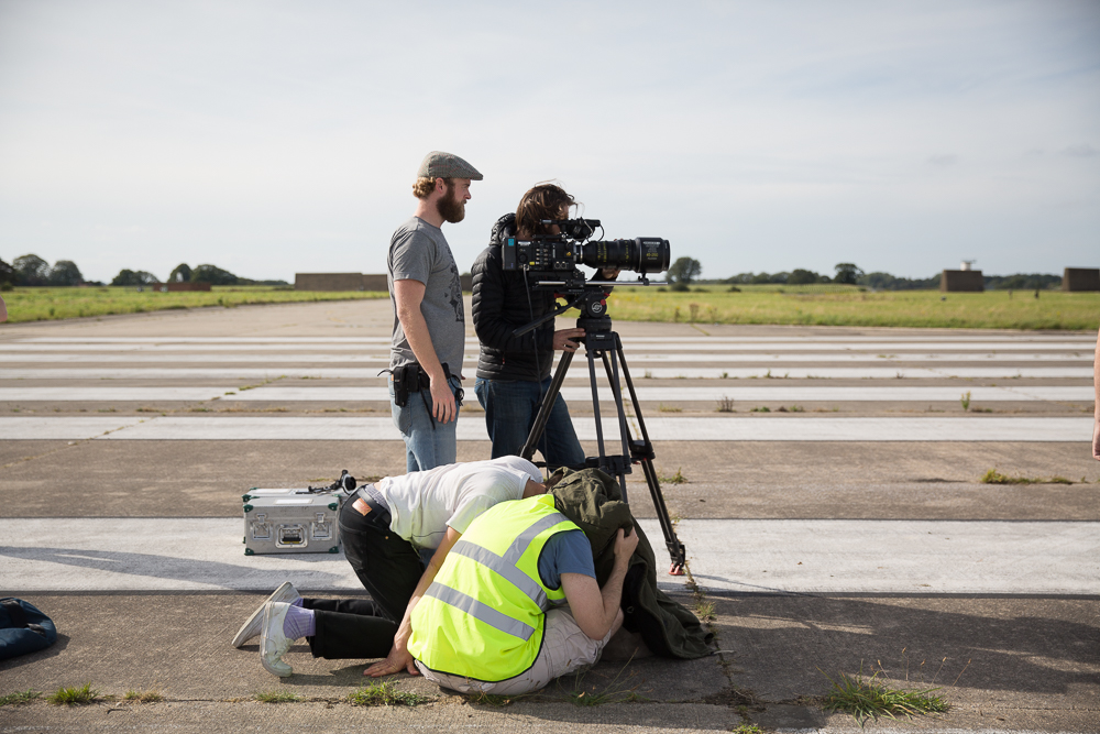 Indie filmmaking crew on set on an airfield