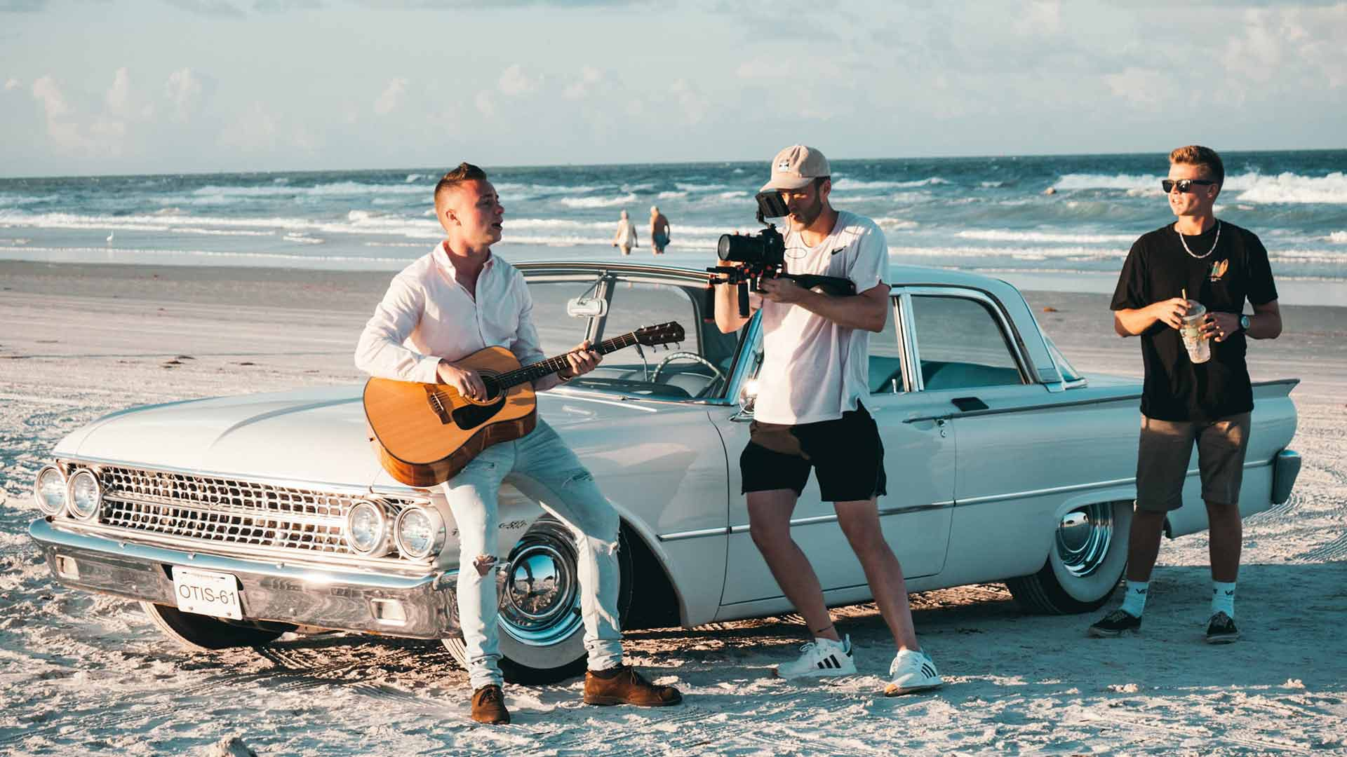 Musician playing guitar on a vintage Cadillac at the beach with filmmaker shooting footage for a music video -music video and short film ideas