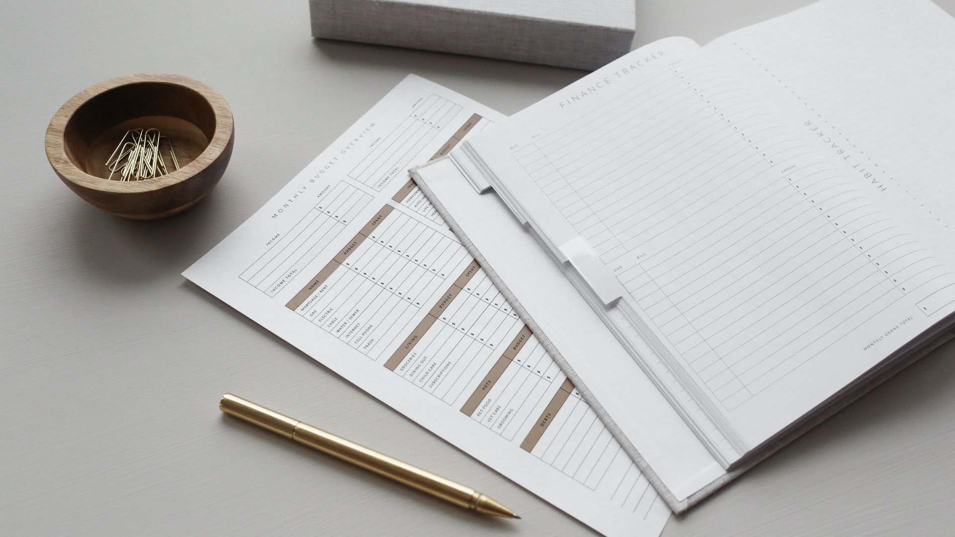 budgeting documents on table with pen and paperclips