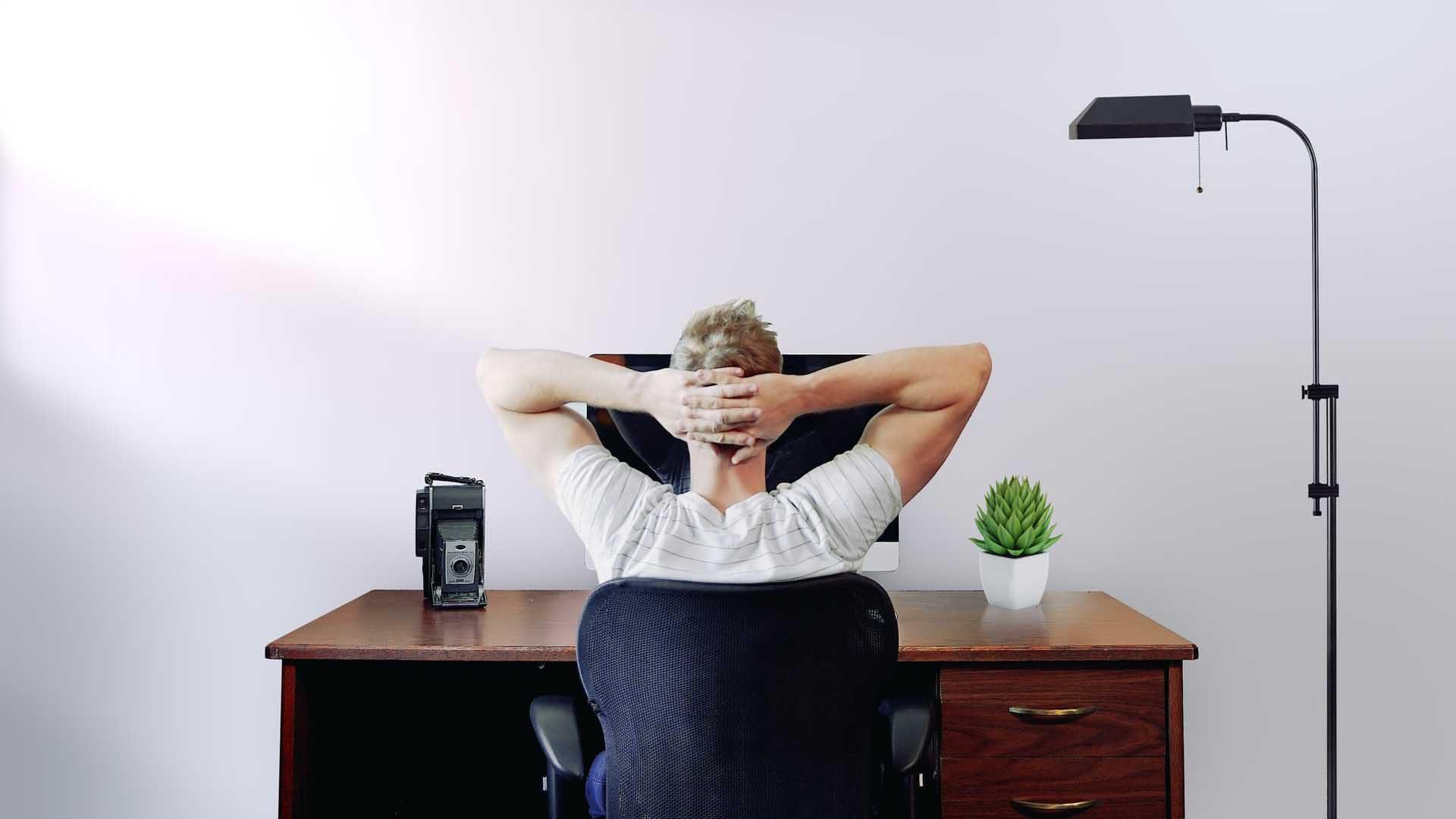 Idea development - man sitting at desk with hands behind head (thinking)