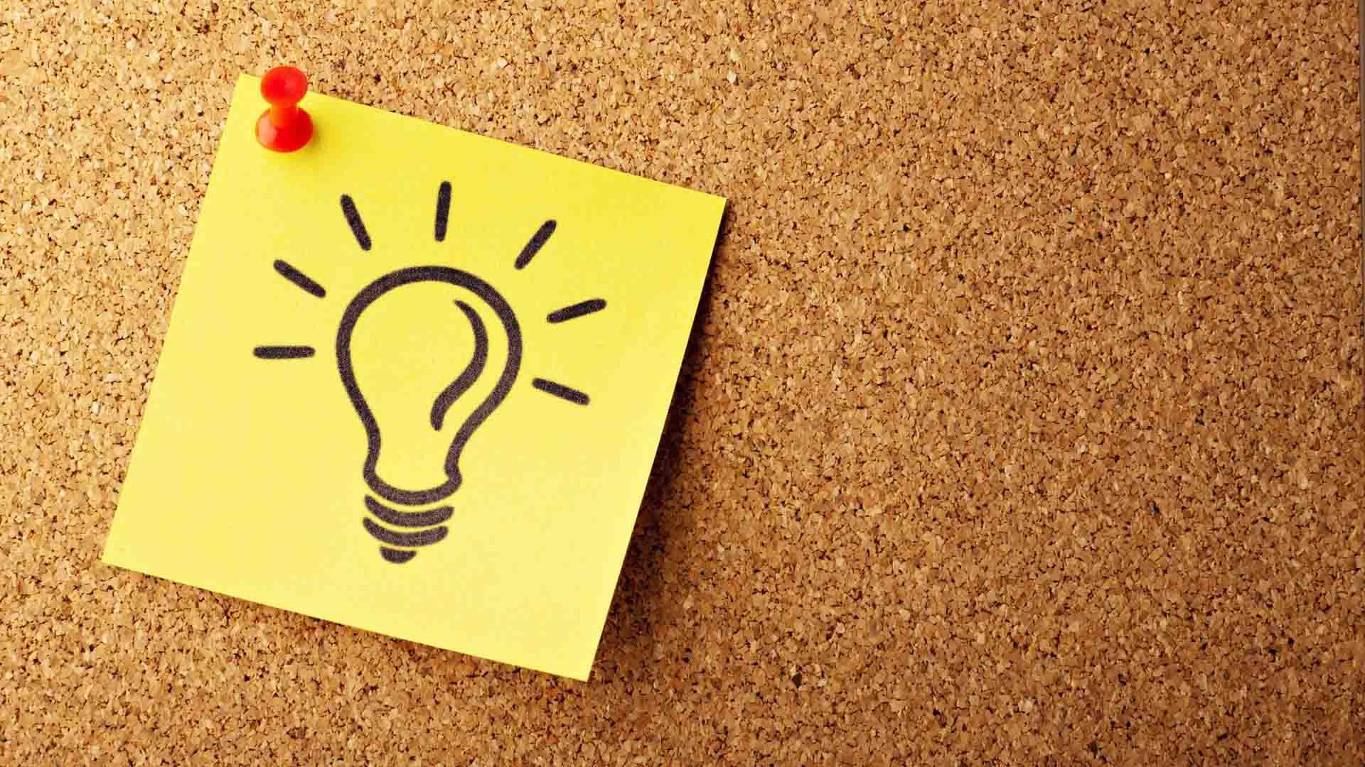 idea generation - post-it note with lightbulb drawn on it on cork ideas board